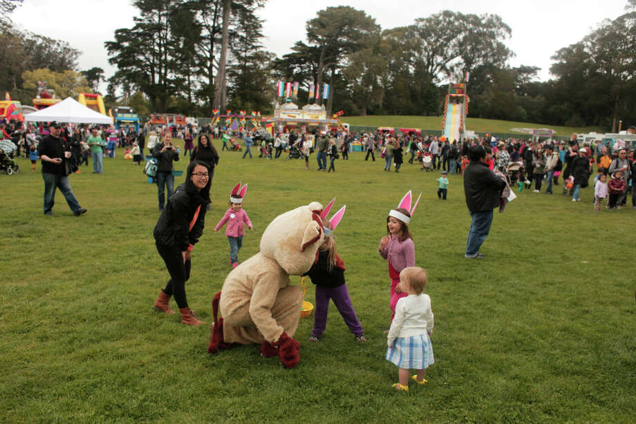 Children play with a volunteer in a costume during the Eggstravaganza festival held in Golden Gate Park on Saturday. The bash featured carnival rides and games, and a visit with the Easter Bunny. Photo: James Tensuan, The Chronicle / ONLINE_YES