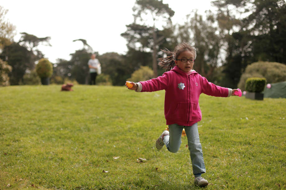 Anisha Hu runs through Golden Gate Park during the Eggstravaganza after finding hidden eggs in the egg hunt on Saturday. Photo: James Tensuan, The Chronicle / ONLINE_YES