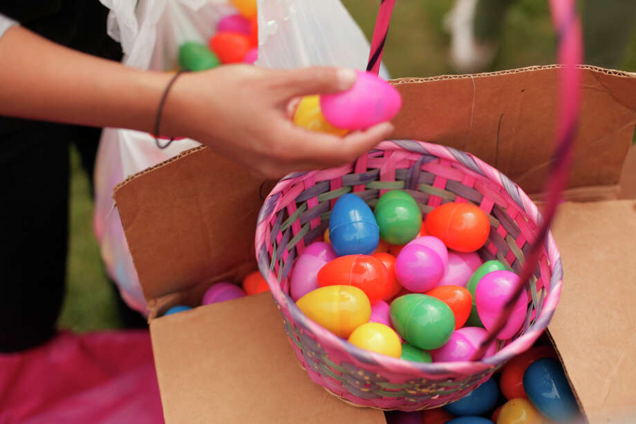 A volunteer loads up baskets with eggs to be given to kids at the Eggstravaganza held in Golden Gate Park on Saturday. Photo: James Tensuan, The Chronicle / ONLINE_YES