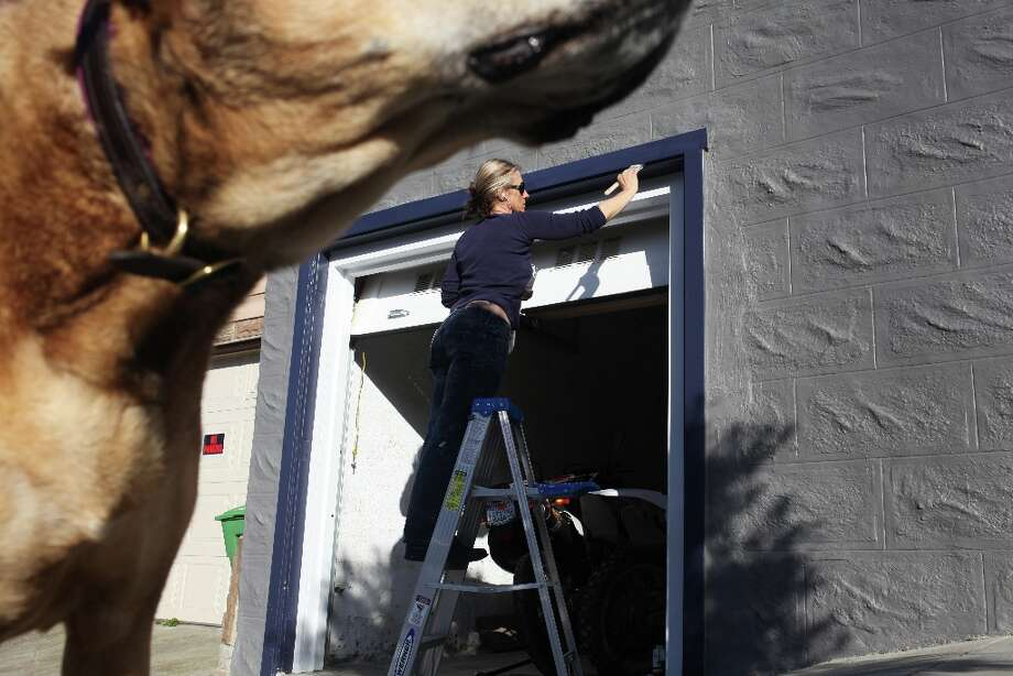Oona Nelson, who has lived in the neighborhood since 2005, paints the trim on her garage as her dog, Carrot, gazes up the Excelsior Heights hill on March 24, 2013 in San Francisco, Calif. Photo: Pete Kiehart, The Chronicle / ONLINE_YES