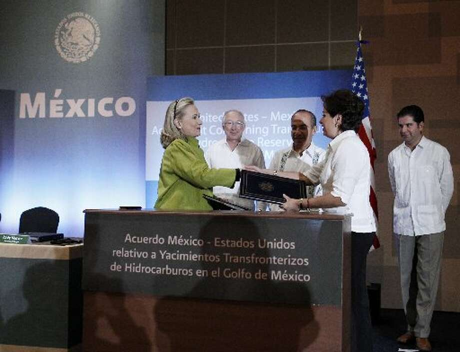 U.S. Secretary of State Hillary Rodham Clinton shakes hands with Mexico's Foreign Minister Patricia Espinosa. Behind them are Interior Secretary Ken Salazar, (second from left), Mexico's President Felipe Calderon (center), and Mexico's Secretary of Energy Jordy Herrera. Clinton and Esinosa signed the United States-Mexico Agreement Concerning Transboundary Hydrocarbon Reservoirs in the Gulf of Mexcio during the G20 foreign ministers summit in Los Cabos, Mexico on February 20, 2012.