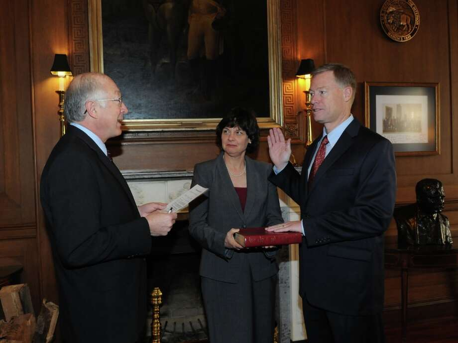 Interior Secretary Ken Salazar officiates as Retired Rear Adm. James Watson is sworn in as director of the Bureau of Safety and Environmental Enforcement, with his wife Anne Watson, holding a Bible.