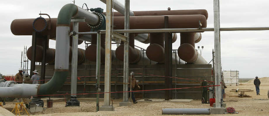 Workers gather by the slugcatchers as work continues at the Anadarko Brasada Gas Plant in La Salle County south of Cotulla. The slug collectors is the first process for natural gas coming in from the Eagle Ford Shale field in the pipeline on the lower left. Slugs are a term used for gas that condense during the transportation through the pipelines.