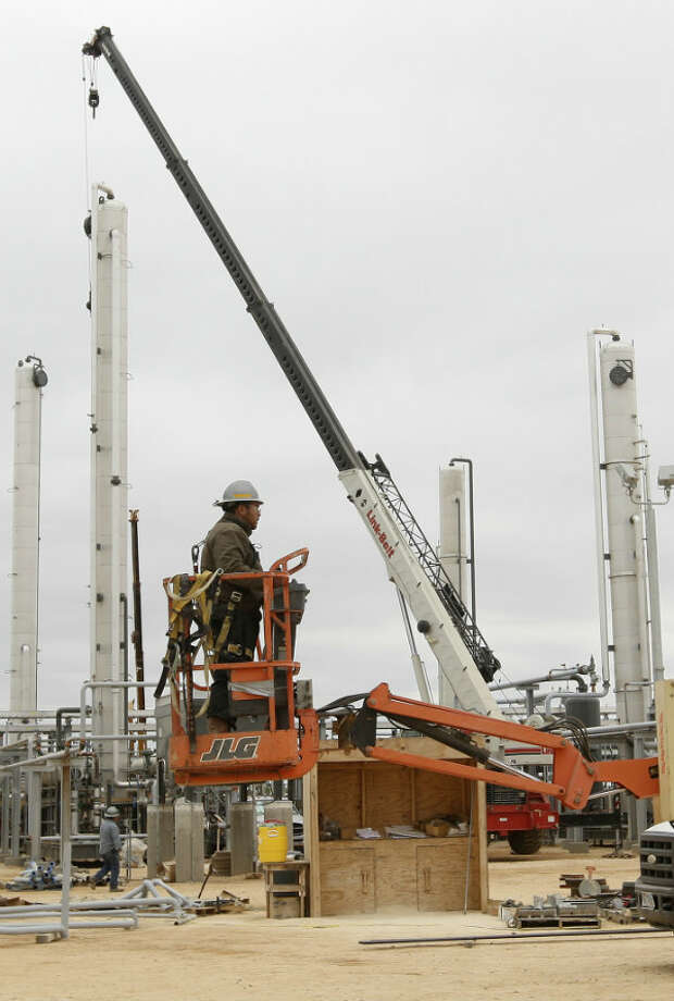 A worker moves a lift as work continues at the Anadarko Brasada Gas Plant in La Salle County south of Cotulla.