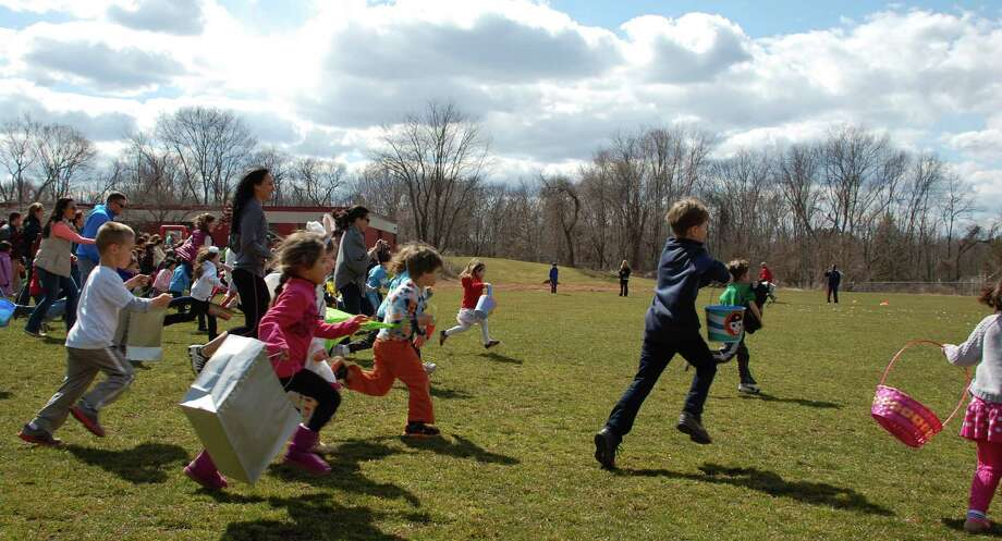 Kids scramble across the fields at Long Lots School on Saturday in search of tasty treats at the Greens Farms Volunteer Fire Department's 62nd annual egg hunt.  WESTPORT NEWS, CT 3/30/13 Photo: Jarret Liotta / Westport News contributed