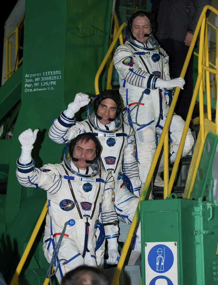 In this image provided by NASA Russian Flight Engineer Alexander Misurkin, top, NASA Flight Engineer Chris Cassidy, and Soyuz Commander Pavel Vinogradov, bottom, wave farewell from the base of the Soyuz rocket at the Baikonur Cosmodrome in Baikonur, Kazakhstan, Friday, March 29, 2013.  It was the first time a space crew has taken such a direct route to the orbiting lab. Cassidy, Vinogradov and Misurkin are the first crew to reach the station after only four orbits instead of the standard 50-hour flight to reach the station. Photo: AP