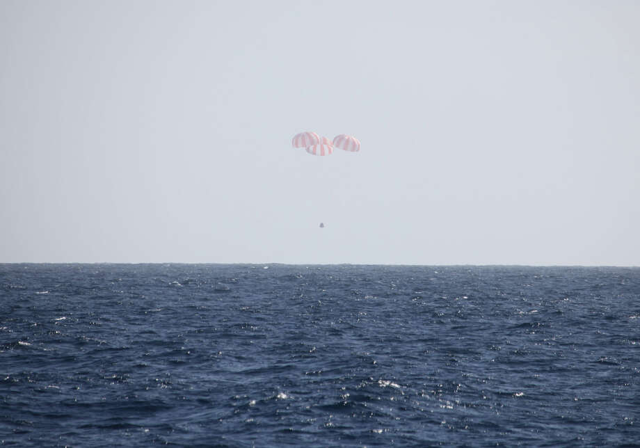 In this image provided by SpaceX, the Dragon capsule uses parachutes to descend to the Pacific Ocean off the coast of Mexico's Baja Peninsula after leaving the International Space Station. The vehicle brought back more than 1 ton of science experiments and old station equipment. It's the only supply ship capable of two-way delivery. NASA is paying SpaceX more than $1 billion for a dozen resupply missions. Photo: AP