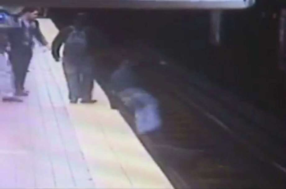 In this still image taken from security video provided by the Southeastern Pennsylvania Transportation Authority (SEPTA), Christopher Knafelc jumps off a subway platform in north Philadelphia to help a man who fell onto the tracks Thursday afternoon. Knafelc, 32, jumped down to help the man, knowing that a train would be arriving in a few minutes. Train traffic was halted and the man was taken to a hospital and listed in stable condition. Photo: AP