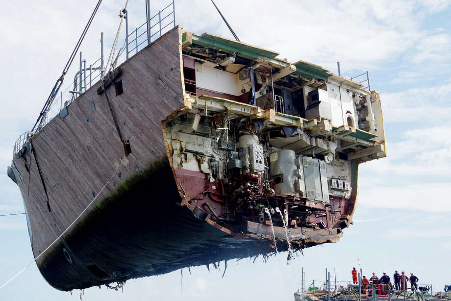 The bow of the USS Guardian, a US Navy minesweeper, is lifted on Tuesday by a crane during a continuing salvage operation off Tubbataha Reef, a World Heritage Site in the Sulu Sea, 400 miles southwest of Manila, Philippines. The ship ran aground before dawn on Jan. 17, damaging coral reef. (AP Photo/Philippine Coast Guard)  Photo: AP