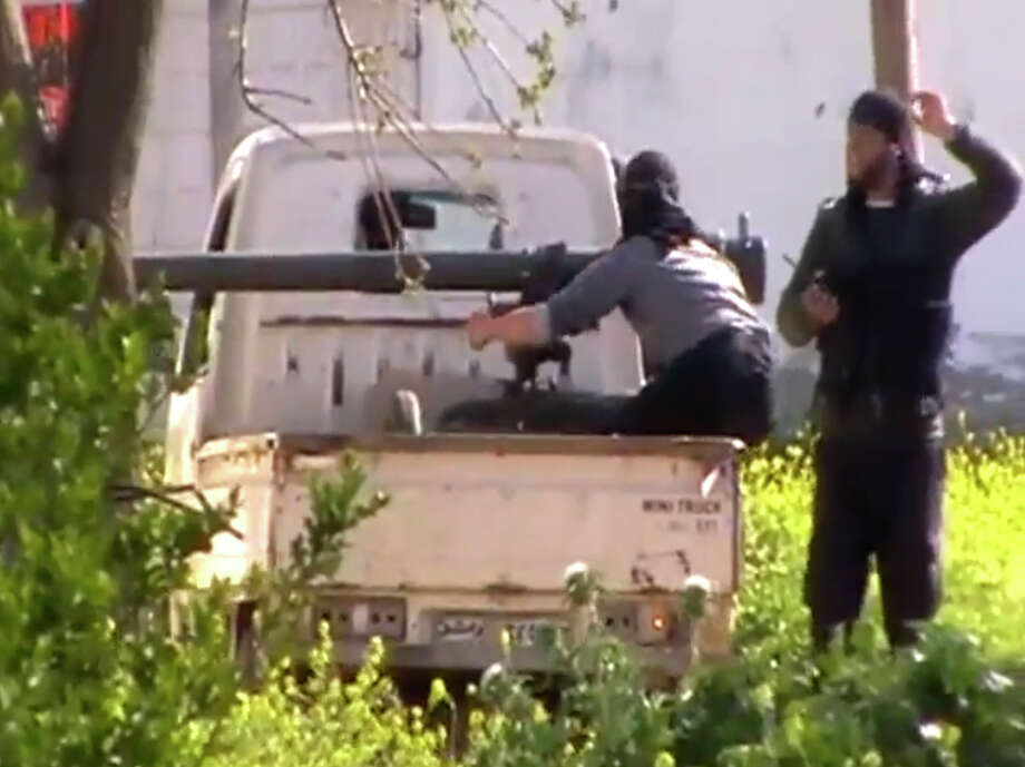 In this Thursday image taken from video obtained from the Shaam News Network, which has been authenticated based on its contents and other AP reporting, shows fighters from the Syrian Free Army preparing to fire on the regime's army in Dael less than 15 kilometers (10 miles) from the Jordanian border in Daraa province. Syrian rebels on Friday captured a strategic town near the border with Jordan after a day of fierce clashes that killed dozens of people, activists said, as opposition fighters expand their presence in the south, considered a gateway to Damascus. Photo: AP