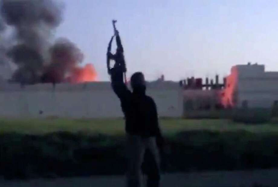 In this Thursday image taken from video obtained from the Ugarit News, which has been authenticated based on its contents and other AP reporting, shows a building at the  Syrian government checkpoint on fire, in Dael less than 15 kilometers (10 miles) from the Jordanian border in Daraa province, Syria. Thursday, March 28, 2013. Syrian rebels on Friday captured a strategic town near the border with Jordan after a day of fierce clashes that killed dozens of people, activists said, as opposition fighters expand their presence in the south, considered a gateway to Damascus. Photo: AP