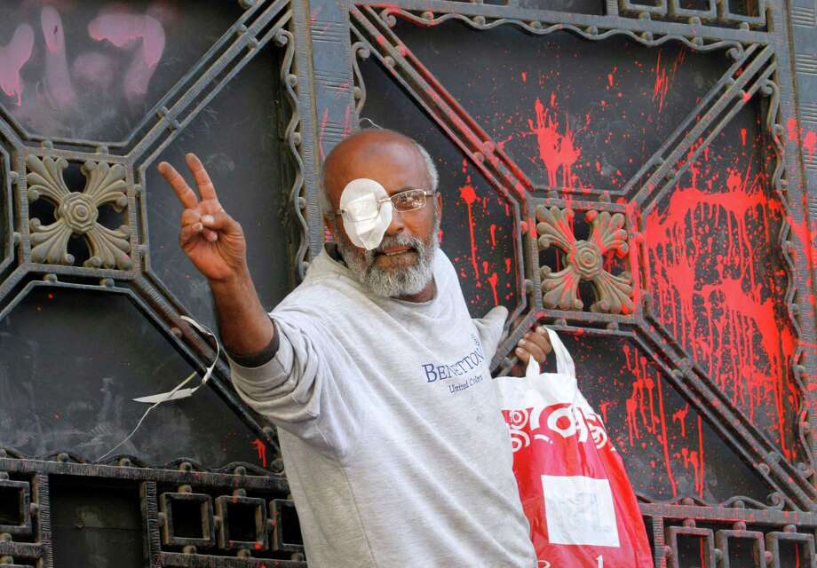 An Egyptian protester, who says he lost his eye during last month's clashes with security forces, flashes the victory sign in front of the door of prosecutor general, which was stained in red by protesters, during a protest in Cairo, Egypt, Friday. Hundreds of activists demonstrated to show solidarity with political activists charged by the prosecutor general with inciting violence during last week's clashes near the Muslim Brotherhood's Cairo headquarters. Photo: AP