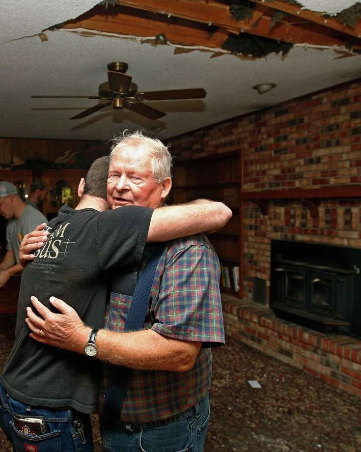 Joe Reneau, right, gets a hug from friend Cody Parsons in his family room in Sparks, Okla. on Sunday, Nov. 6, 2011 after the room was damaged when the chimney collapsed during an earthquake and fell partially through the roof, at upper right. Neither Joe nor his wife were in the room at the time, and were not injured. A team of scientists have determined that a 5.6 magnitude quake in Oklahoma in 2011 was caused when oil drilling waste was injected deep underground. The report was released Tuesday, March 26, 2013 by the journal Geology. That makes it the most powerful quake to be blamed on deep injections of wastewater, although not everyone agrees. Oklahoma's state seismologists say the quake was natural. Photo: AP