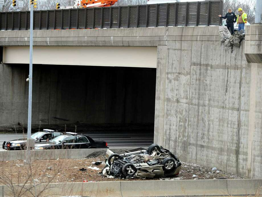A Windsor Conn. police sergeant and a worker with the Connecticut Department of Transportation, look down at the crash scene below from the Route 305 overpass after an SUV crashed through the wall and plunged onto the median of I-91 in Windsor, Tuesday, March 26, 2013. The accident happened around 10 a.m. after the vehicle crashed through the wall of the overpass bridge landing upside down in the median between the north and south bound lanes of I-91 trapping the male driver inside. The unidentified man was transported in critical condition to  Hartford Hospital, Windsor Police Captain Thomas LePore said. Photo: AP