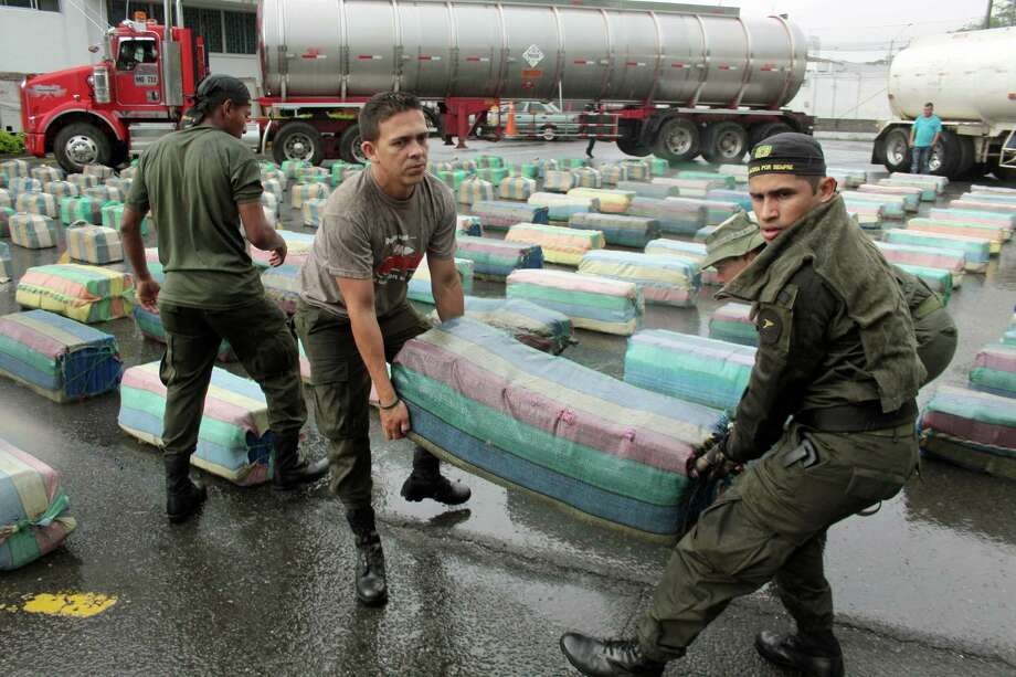 Police officers carry a bulk of seized marijuana to be displayed at a media presentation at police headquarter in Cali, Colombia, Tuesday. According to police the 7.7 tons of marijuana were seized on Monday from the rebels of the Revolutionary Armed Forces of Colombia, FARC, during a raid in a highway near Cali. Photo: AP