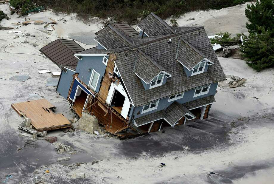More than 4 out of 5 Americans want to prepare now for rising seas and stronger storms from climate change, a new national survey says. But most are unwilling to keep spending money to restore and protect stricken beaches. The poll by Stanford University released Thursday found that only 1 in 3 people favored the government spending millions to construct big sea walls, replenish beaches or pay people to leave the coast. Pictured: 2012 file aerial photo shows a collapsed house along the central Jersey Shore coast. Photo: AP