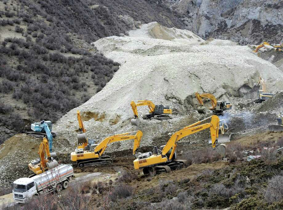 In this photo released by China's Xinhua News Agency, earthmovers remove rocks and mud on the scene where a landslide hit a mining area in Maizhokunggar County of Lhasa, southwest China's Tibet Autonomous Region, on Friday.  The large landslide trapped dozens of workers in the gold mining area, state media reported. (AP Photo/Xinhua, Chogo) Photo: AP