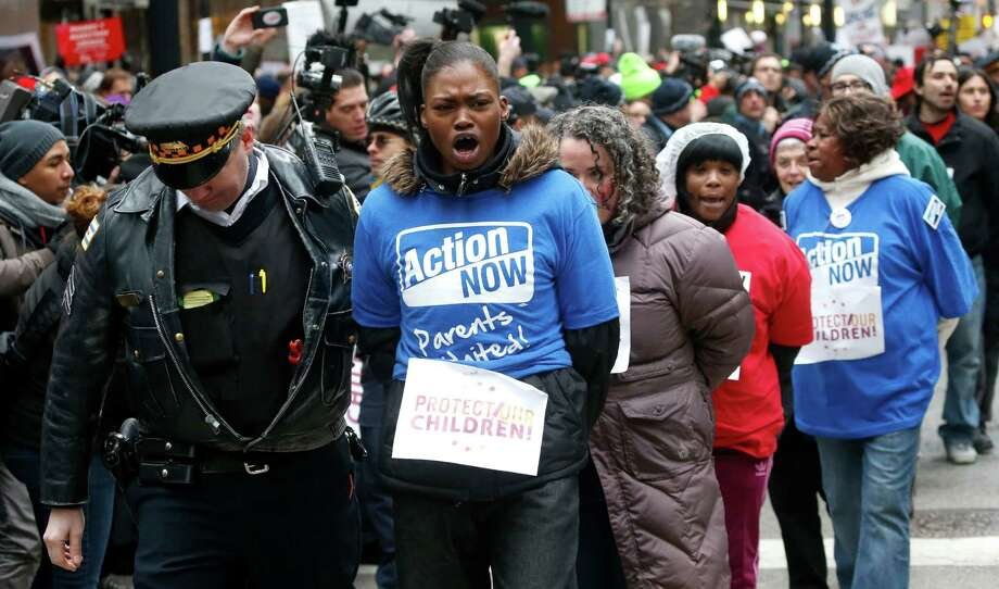 A Chicago police officer takes several protesters into custody during an act of civil disobedience during a march and demonstration of opponents to a plan to close 54 Chicago Public Schools in Chicago's downtown Wednesday. Mayor Rahm Emanuel and schools CEO Barbara Byrd-Bennett say the closings are necessary because too many CPS facilities are half-empty and academically failing. They say shuttering buildings will allow the district to move students to higher quality schools and help trim a $1 billion budget shortfall. Opponents say the plan disproportionately affects minority students and won't save money. Photo: AP