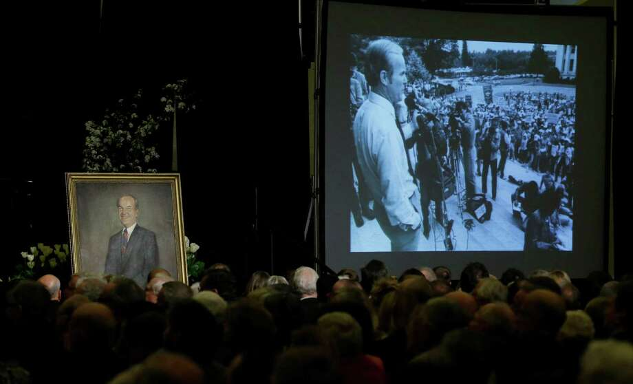 A photograph of former Washington Gov. Booth Gardner at a political event is shown at right, Saturday near a portrait of Gardner, during a video tribute shown at a memorial service in Tacoma, Wash. Gardner served two terms as Governor and died March 15, 2013, at his home in Tacoma. Photo: AP