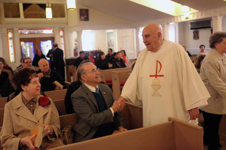 Deacon Joseph Melita greets parishioners Gloria and Jack Rodrigues , of Trumbull, before Easter Mass at St. Margaret Shrine in Bridgeport, Conn. on Sunday, March 31. 2012. Photo: BK Angeletti, B.K. Angeletti / Connecticut Post freelance B.K. Angeletti