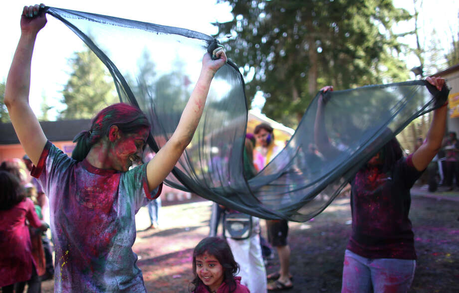 Jaya Wadhwani, left, carries a cloth over the head of Ananya Ray, 4, along with Suneeta Bindal during a celebration of Holi, the Hindu festival of colors on Saturday, March 30, 2013 at the Sanatan Dharma Temple & Cultural Center in Maple Valley. The annual cultural and religious event is a time for Hindus to enjoy spring's abundant colors and say farewell to winter. Photo: JOSHUA TRUJILLO / SEATTLEPI.COM