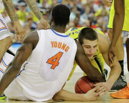 Florida's Patric Young (4) and Michigan's Mitch McGary (4) fight for possession of the ball during the first half of a regional final game in the NCAA college basketball tournament, Sunday, March 31, 2013, in Arlington, Texas. (AP Photo/Tony Gutierrez) Photo: Tony Gutierrez, Associated Press / AP