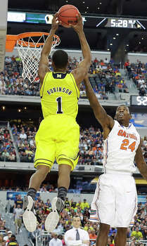 Michigan's Glenn Robinson III (1) shoots as Florida's Casey Prather (24) defends during the first half of a regional final game in the NCAA college basketball tournament, Sunday, March 31, 2013, in Arlington, Texas. (AP Photo/Tony Gutierrez) Photo: Tony Gutierrez, Associated Press / AP