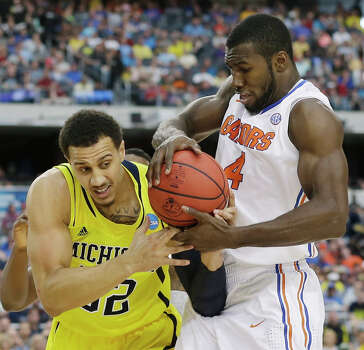 Michigan's Jordan Morgan (52) and Florida's Patric Young (4) fight for possession of the ball during the first half of a regional final game in the NCAA college basketball tournament, Sunday, March 31, 2013, in Arlington, Texas. (AP Photo/Tony Gutierrez) Photo: Tony Gutierrez, Associated Press / AP