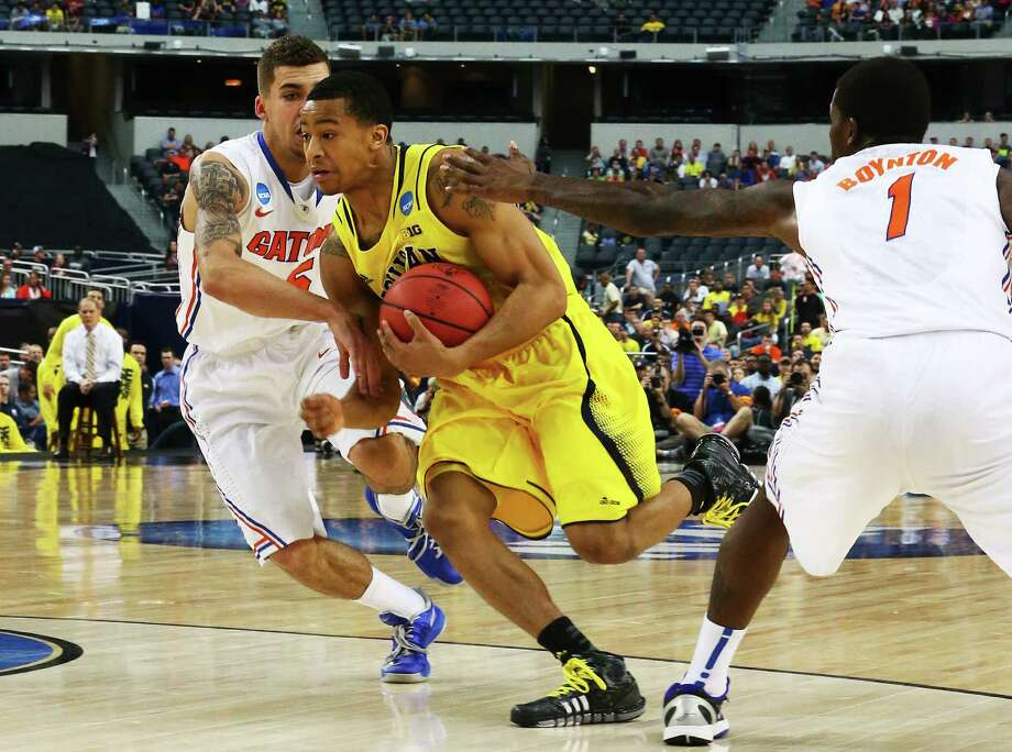 ARLINGTON, TX - MARCH 31:  Trey Burke #3 of the Michigan Wolverines drives between Scottie Wilbekin #5 and Kenny Boynton #1 of the Florida Gators in the first half during the South Regional Round Final of the 2013 NCAA Men's Basketball Tournament at Dallas Cowboys Stadium on March 31, 2013 in Arlington, Texas. Photo: Ronald Martinez, Getty Images / 2013 Getty Images
