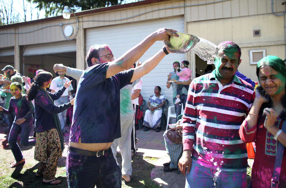 A participant throws water on a couple during a celebration of Holi, the Hindu festival of colors on Saturday, March 30, 2013 at the Sanatan Dharma Temple & Cultural Center in Maple Valley. The annual cultural and religious event is a time for Hindus to enjoy spring's abundant colors and say farewell to winter. Photo: JOSHUA TRUJILLO / SEATTLEPI.COM
