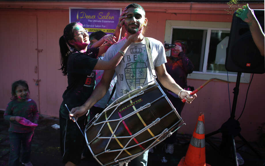 Gary Brar plays a Punjabi drum as others coat him in color during a celebration of Holi, the Hindu festival of colors on Saturday, March 30, 2013 at the Sanatan Dharma Temple & Cultural Center in Maple Valley. The annual cultural and religious event is a time for Hindus to enjoy spring's abundant colors and say farewell to winter. Photo: JOSHUA TRUJILLO / SEATTLEPI.COM
