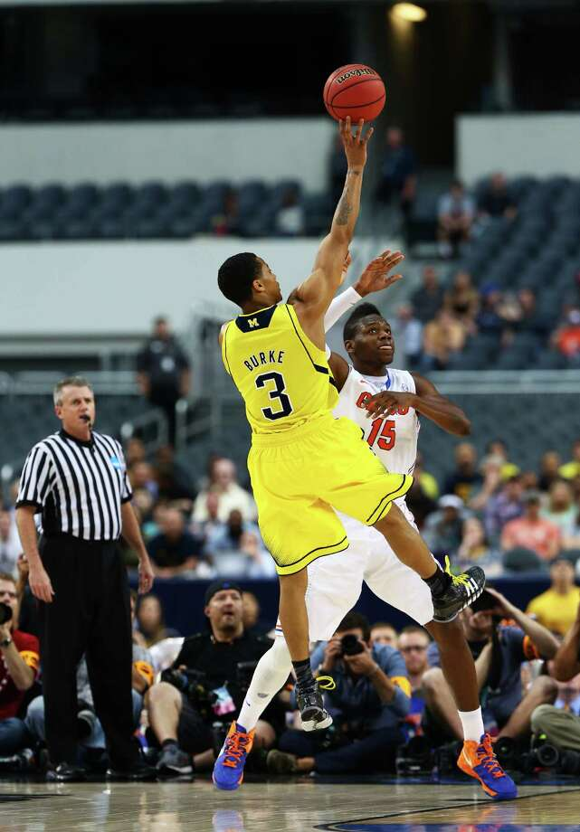 ARLINGTON, TX - MARCH 31:  Trey Burke #3 of the Michigan Wolverines shoots ovre Will Yeguete #15 of the Florida Gators in the first half during the South Regional Round Final of the 2013 NCAA Men's Basketball Tournament at Dallas Cowboys Stadium on March 31, 2013 in Arlington, Texas. Photo: Tom Pennington, Getty Images / 2013 Getty Images