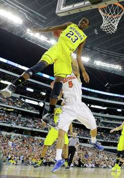 Michigan guard Caris LeVert (23) blocks a shot by Florida guard Scottie Wilbekin (5)during the first half of a regional final game in the NCAA college basketball tournament, Sunday, March 31, 2013, in Arlington, Texas. (AP Photo/David J. Phillip) Photo: David J. Phillip, Associated Press / AP