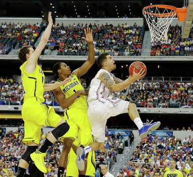 Florida's Scottie Wilbekin (5) shoots as Michigan's Glenn Robinson III (1) and Nik Stauskas (11) defend during the first half of a regional final game in the NCAA college basketball tournament, Sunday, March 31, 2013, in Arlington, Texas. (AP Photo/David J. Phillip) Photo: David J. Phillip, Associated Press / AP
