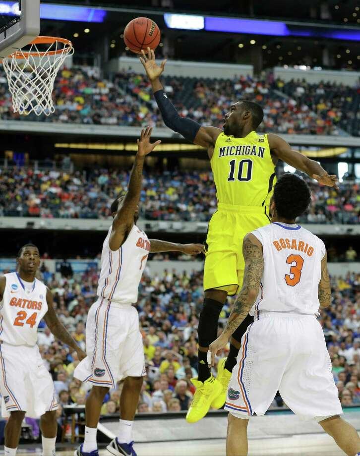 Michigan's Tim Hardaway Jr. (10) shoots past Florida's Kenny Boynton (1) and Mike Rosario (3) during the first half of a regional final game in the NCAA college basketball tournament, Sunday, March 31, 2013, in Arlington, Texas. Florida's Casey Prather (24) looks on. (AP Photo/Tony Gutierrez) Photo: Tony Gutierrez, Associated Press / AP