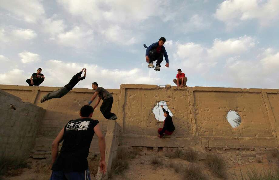 Palestinian youths practice their parkour skills in KhanYounis, southern Gaza Strip , Sunday, March 31, 2013. Parkour is a physical discipline of movement focused on overcoming obstacles. Training is held at cemeteries in KhanYounis. (AP Photo / Hatem Moussa) Photo: Hatem Moussa, Associated Press / AP