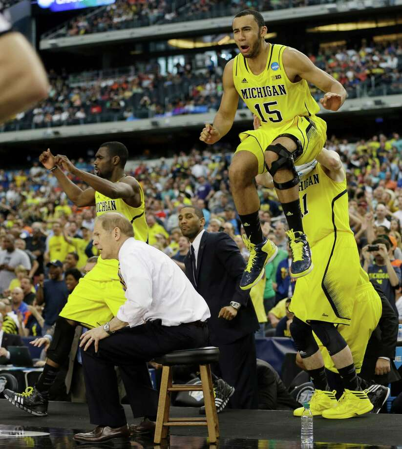 Michigan head coach John Beilein and players including Jon Horford (15) react against Florida during the second half of a regional final game in the NCAA college basketball tournament, Sunday, March 31, 2013, in Arlington, Texas. Michigan won 79-59. (AP Photo/David J. Phillip) Photo: David J. Phillip, Associated Press / AP