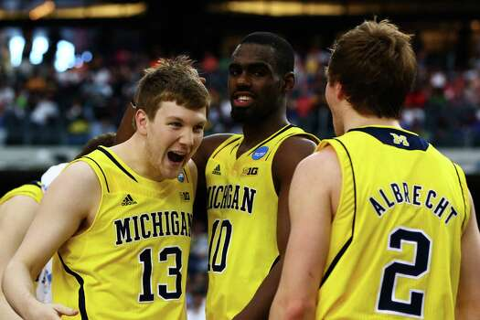 ARLINGTON, TX - MARCH 31:  Matt Vogrich #13, Tim Hardaway Jr. #10 and Spike Albrecht #2 of the Michigan Wolverines celebrate their 79 to 59 win over the Florida Gators during the South Regional Round Final of the 2013 NCAA Men's Basketball Tournament at Dallas Cowboys Stadium on March 31, 2013 in Arlington, Texas. Photo: Tom Pennington, Getty Images / 2013 Getty Images