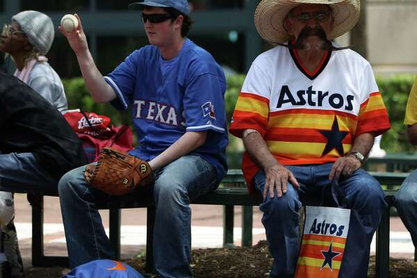 Tony Genna, left, a Texas Ranger fan sits next Valentin Jalomo, an Astros fan, right, during the street festival outside of Minute Maid Park, before the start of Opening Day Sunday, March 31, 2013, in Houston.