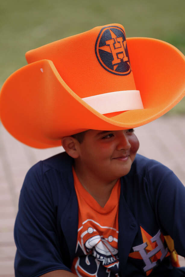 Brandon West, 11, wears a giant Astros hat during the street festival. Photo: Karen Warren, Houston Chronicle / © 2013 Houston Chronicle