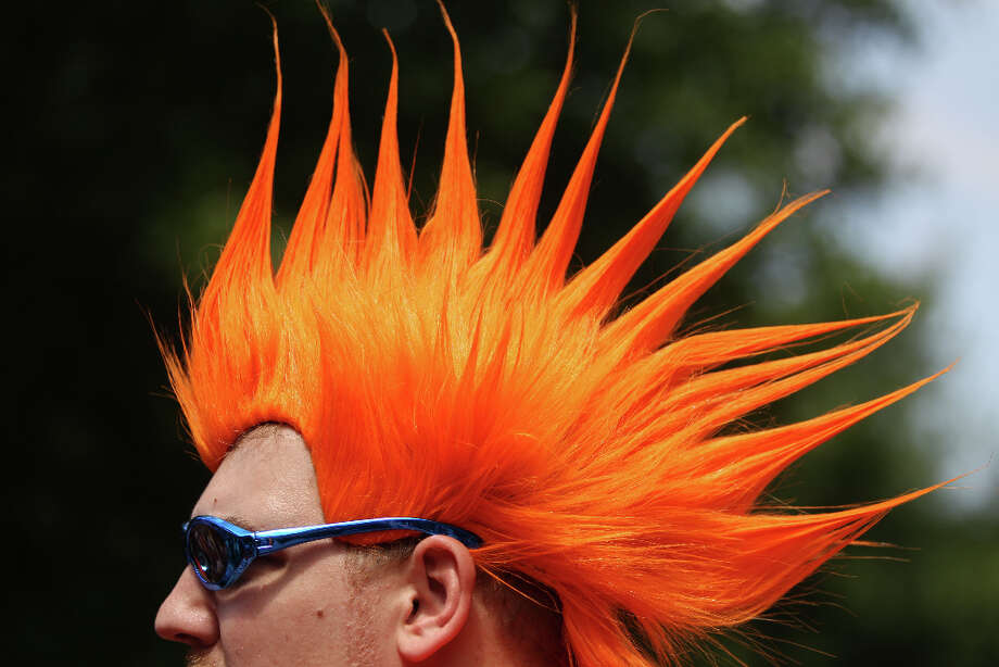 Chad Carlson, of Nederland, wears an orange wig and blue glasses during the street festival. Photo: Karen Warren, Houston Chronicle / © 2013 Houston Chronicle