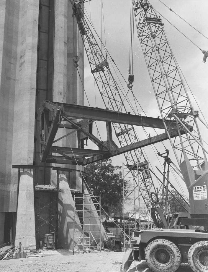 "From caption published in the Express on Aug. 17, 1967: ""Workmen hoist into place one of 12 sections of steel superstructure for the fifth and sixth floors of the Tophouse around the base of the Tower of [the] Americas. Fastened by some 14,000 feet of steel rods to hydraulic jacks high above at the 605-foot level, the Tophouse will be lifted after the superstructure for the two top floors is complete and the fourth floor steel will be installed, and so on until the entire six floors are complete."" Photo: San Antonio Express-News File Photo"