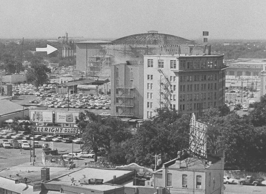 "From the caption published in the News on May 24, 1967: ""The Tower of the Americas was creeping up Tuesday [May 23] and was easily visible from the Express Publishing Co. building at Avenue E and Third. By the end of the week the tower is due to rise above the roof of the convention center [arena] roof shown [behind] the Crockett Hotel. The tower will be better than 100 feet tall by Sunday [May 28] and should be easily visible except where shielded by tall buildings. The tower was 65 feet off the ground Wednesday [May 24]."" The arrow points to the tower construction. Photo: San Antonio Express-News File Photo"