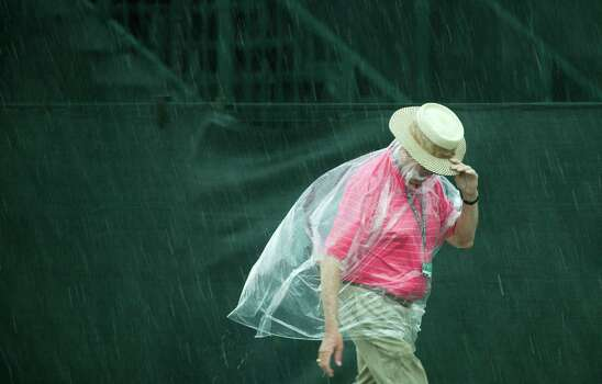 A golf fan walks off the course as play in the final round of the Shell Houston Open is suspended by weather at the Redstone Tournament Course Sunday, March 31, 2013, in Humble. Photo: Brett Coomer, Houston Chronicle / © 2013 Houston Chronicle