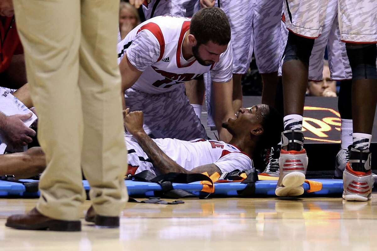INDIANAPOLIS, IN - MARCH 31: Kevin Ware #5 of the Louisville Cardinals talks with teammate Luke Hancock #11 as Ware is tended to by medical personnel after he injured his leg in the first half against the Duke Blue Devils during the Midwest Regional Final round of the 2013 NCAA Men's Basketball Tournament at Lucas Oil Stadium on March 31, 2013 in Indianapolis, Indiana.