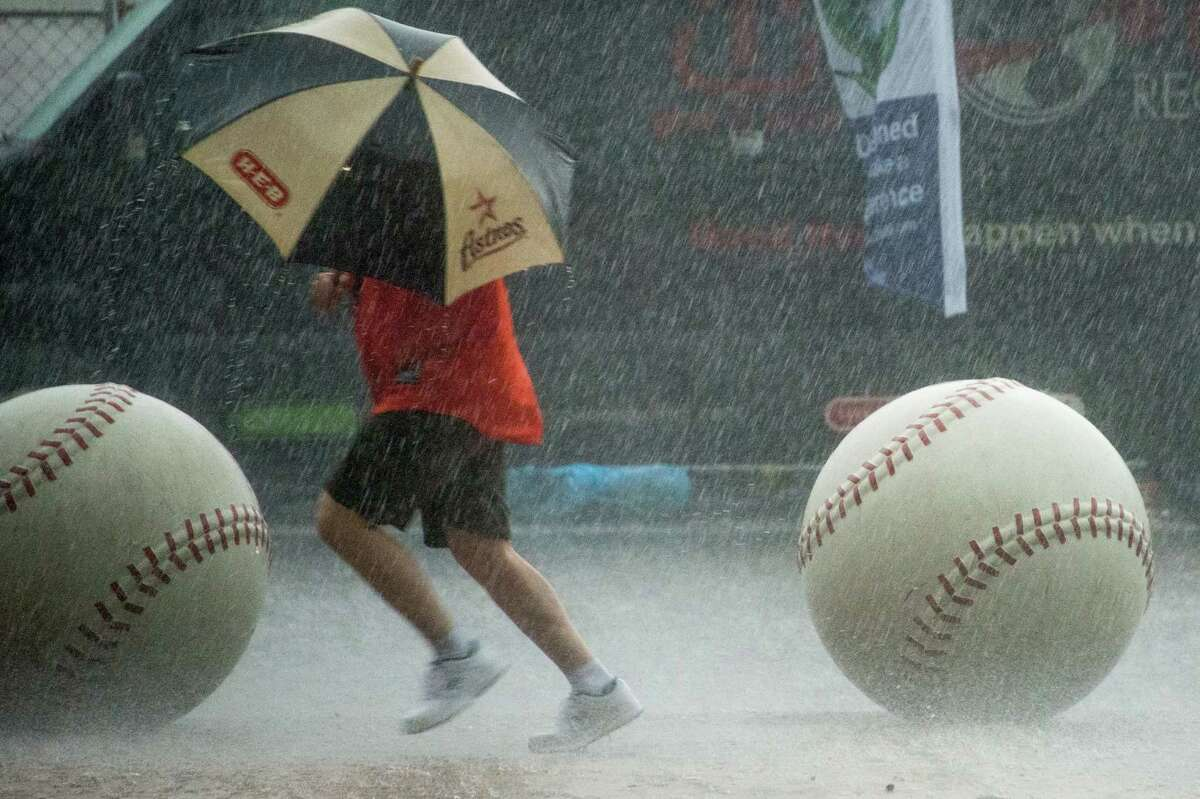 A Houston Astros fan runs for the stadium in a downpour before the Astros season opener against the Texas Rangers at Minute Maid Park on Sunday, March 31, 2013, in Houston.