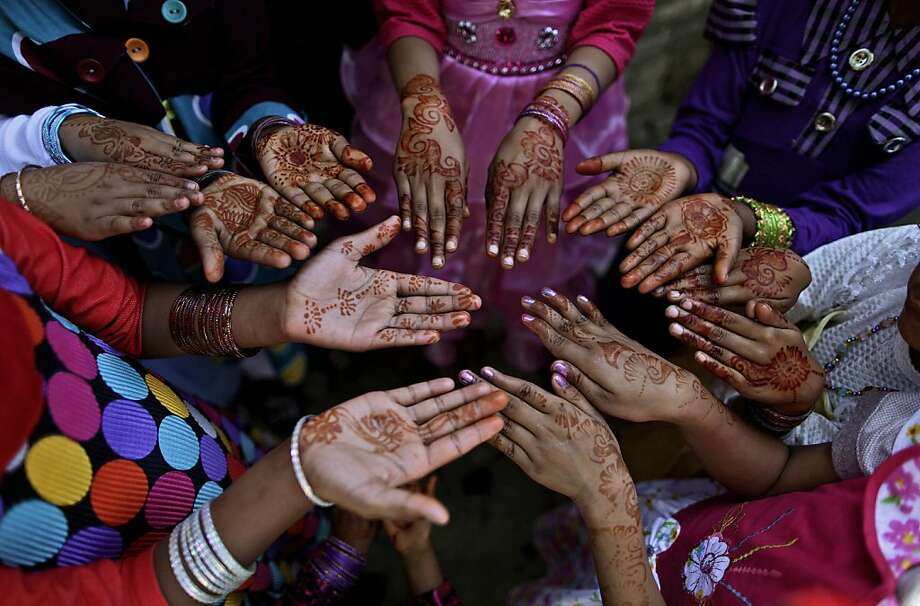 Pakistani Christian girls, display their hands decorated with Bangles and painted with Henna paste as they celebrate Easter holiday following a mass at in a Christian neighborhood in Islamabad, Pakistan, Sunday, March 31, 2013. Pakistan's Christians, are celebrating Easter along with other Christian nations. (AP Photo/Muhammed Muheisen) Photo: Muhammed Muheisen, Associated Press