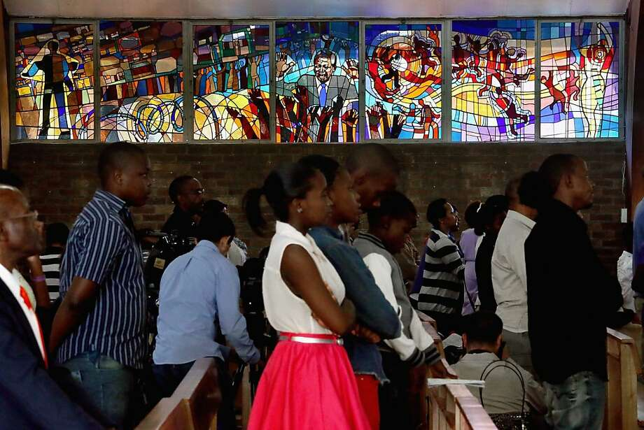 "JOHANNESBURG, SOUTH AFRICA - MARCH 31:  Former South African President Nelson Mandela and the struggle against apartheid are depicted in a stained glass window as congregants pray during Easter services at Regina Mundi Catholic Church in the Soweto area March 31, 2013 in Johannesburg, South Africa. A central gathering place during he anti-apartheid struggle, the church held prayers for former South African President Nelson Mandela, 94, who is in the hospital for the third time since December with lung problems. Referring to Mandela by clan name, Madiba, President Jacob Zuma said, ""We appeal to the people of South Africa and the world to pray for our beloved Madiba and his family and to keep them in their thoughts."" Mandela's lungs were damaged when he contracted tuberculosis during his 27 years in the infamous Robben Island prison. Mandela became the nation's first democratically elected president in 1994 following the end of apartheid.  (Photo by Chip Somodevilla/Getty Images) Photo: Chip Somodevilla, Getty Images"