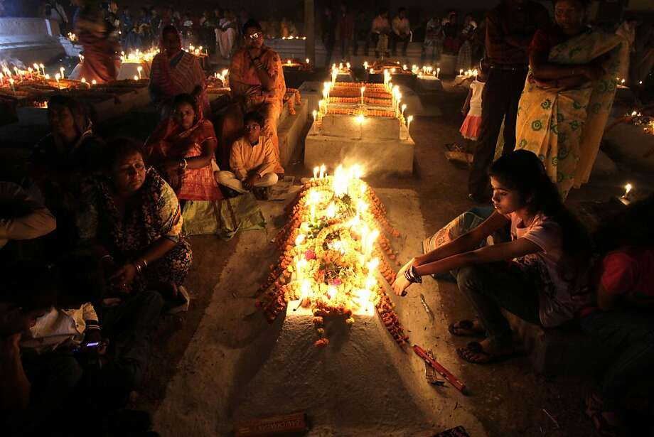Indian Christians light candles and pray beside the graves of their dear ones early morning as they observe Easter in Purulia, about 350 kilometers (220 miles) west of Kolkata, India, Sunday, March 31, 2013. (AP Photo/Bikas Das) Photo: Bikas Das, Associated Press