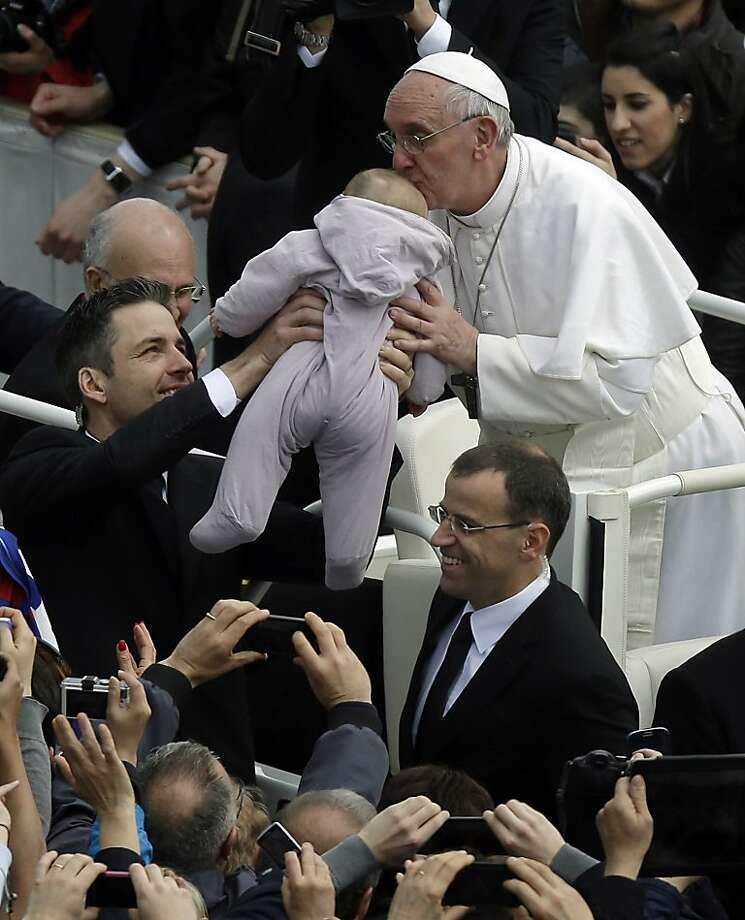 Pope Francis kisses a baby after celebrating his first Easter Mass in St. Peter's Square at the Vatican, Sunday, March 31, 2013. Pope Francis celebrated his first Easter Sunday Mass as pontiff in St. Peter's Square, packed by joyous pilgrims, tourists and Romans and bedecked by spring flowers. Wearing cream-colored vestments, Francis strode onto the esplanade in front of St. Peter's Basilica and took his place at an altar set up under a white canopy. (AP Photo/Gregorio Borgia) Photo: Gregorio Borgia, Associated Press